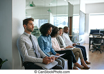 Group of diverse people waiting for interviews in an office