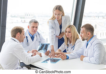 Group of doctors discuss x-ray - Group of doctors look and...