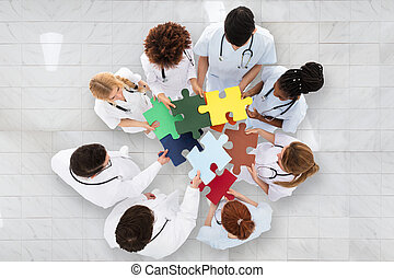 Group Of Doctors Holding Colorful Puzzle