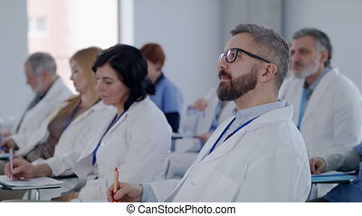 Group of doctors listening to presentation about corona virus on conference.