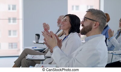 Group of doctors listening to presentation on medical conference.