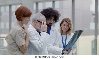 Group of doctors looking at X-ray on medical conference, discussing issues.
