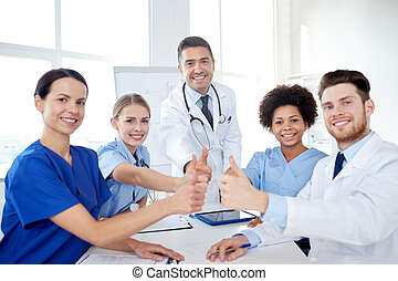 group of doctors showing thumbs up at hospital