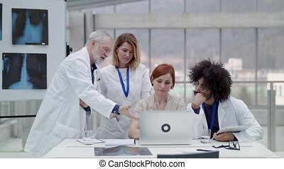 Group of doctors with laptop at the desk discussing issues.
