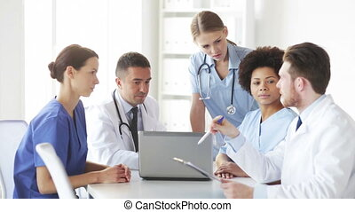 group of doctors with laptop meeting at hospital