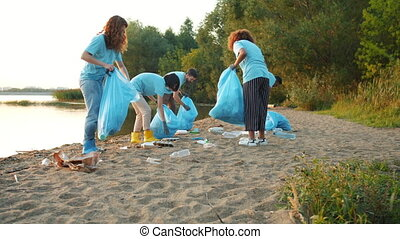 Group of eco activists girls and guys busy picking garbage on lake beach
