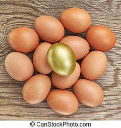 Group of eggs and one golden. At Easter. On a wooden texture...
