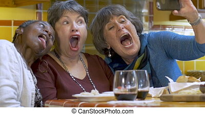 Group of elderly women making funny faces while taking photo...