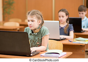 Group of elementary school kids working together in computer class