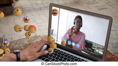 Animation of group of emoji icons flowing over man on laptop screen during video call in the office Global business online network interface concept digital composite.