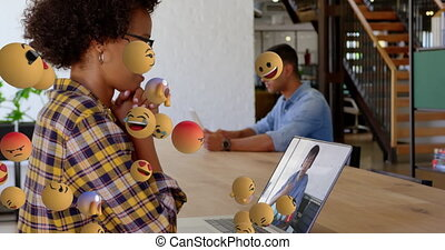 Animation of group of emoji icons flowing over woman using laptop during video call in the office. Global business online network interface concept digital composite.