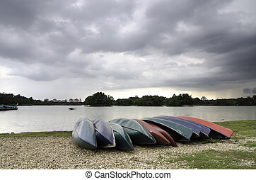 group of empty kayaks on the shore of the lake with dramatic clouds