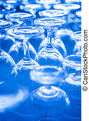 Group of empty wine glass upside down in row blue tone