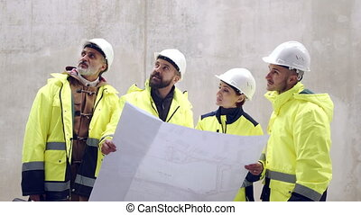 Group of engineers with blueprints against concrete wall on construction site.