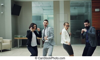 Group of excited young people is dancing in hall of modern business center enjoying corporate party and having fun. Men and women are wearing smart suits.