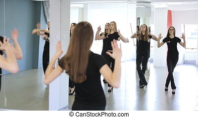 Group of female models in black are learning dance