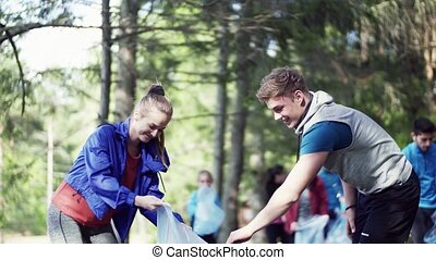 A group of fit young people picking up litter in nature, a plogging concept.