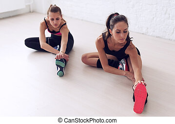 Group of fit women working stretching leg muscles back to warm up at gym fitness, sport, training and lifestyle concept.