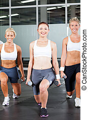 woman using dumbbells in gym