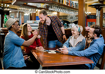 Group of five friends having a meeting in cafe together. Two women and three men at cafe talking laughing and enjoying their time.