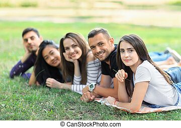 Group of five friends lying in row in park