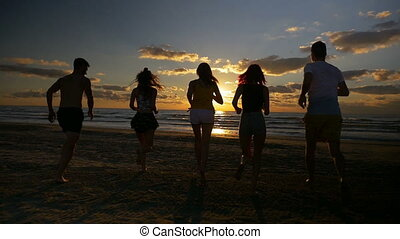 Group of five friends running together towards the sea on a...