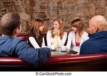 Group of five people having fun in cafe