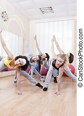 Group of Five Professional Sportswomen Making Stretching Exercises with Trunk Bending in Sport Class.