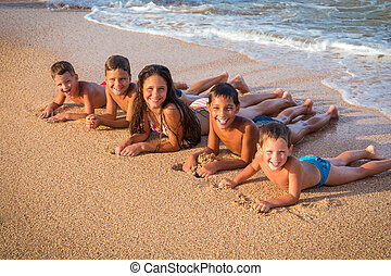 Group of five smiling kids lying down on the beach