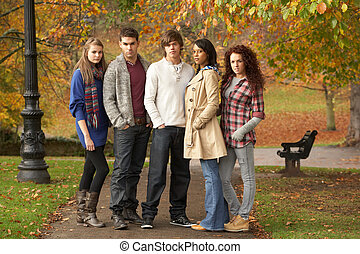Group Of Five Teenage Friends Having Fun In Autumn Park