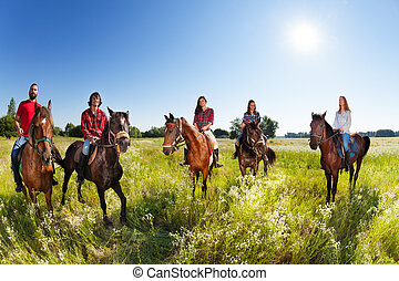 Group of five young people enjoy riding horses