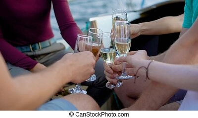 Group of four friends chilling on a yacht while sailing the sea giving speeches and drinking champagne