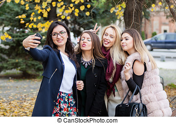 Group of four girl friends taking a selfie in the city