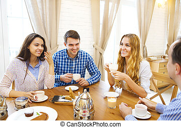Group of four happy friends meeting and talking and eating desserts