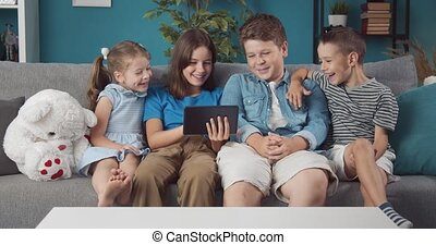 Group of four happy kids sitting on couch and using tablet