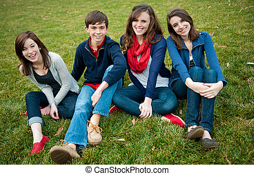 Group of Four happy teenagers outside
