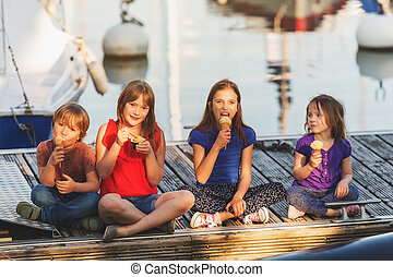 Group of four kids, 3 girls and one boy, eating ice cream outdoors, resting on a pier by the lake