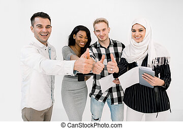 Group of four multiracial students or business partners, Muslim and African women, two Caucasian men, smiling and standing together, showing their thumbs up, isolated on white background