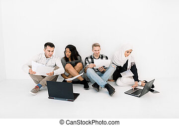 Group of Four young creative Multiethnic People Planning a New Project, talking each other, using laptop and tablet, while sitting on the floor on white background