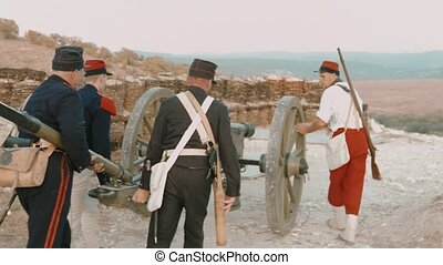 Group of French soldiers rolling out the cannon for the shot