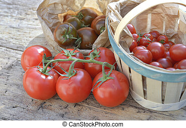 group of fresh tomatoes in crate and basket on a wooden table