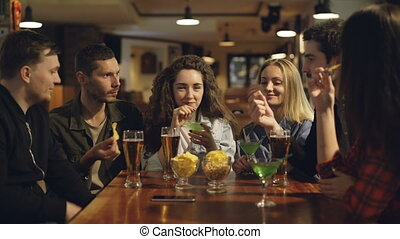 Group of friends are drinking, eating snacks and talking while sitting at table in bar. Young people enjoying themselves and communicating in pub concept.