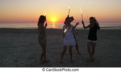 Group of friends celebrating with sparklers on the beach at sunrise