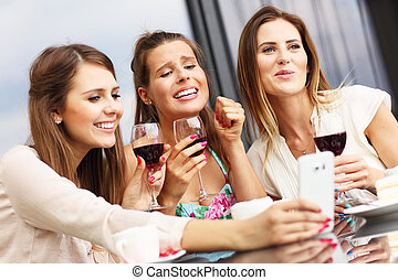 Group of friends chatting in cafe and using smartphone