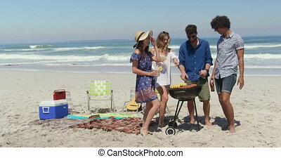 Front view of multi ethnic friends cooking food on barbecue while smiling and having fun at beach on a sunny day 4k