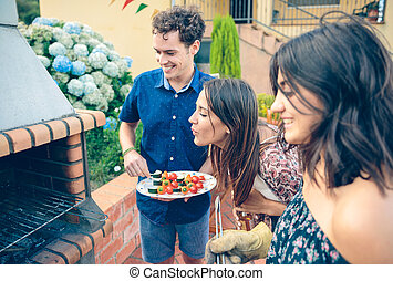 Group of friends cooking in a summer barbecue - Group of...