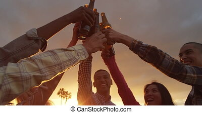 Group of friends drinking a beer on a rooftop - Multi-ethnic...