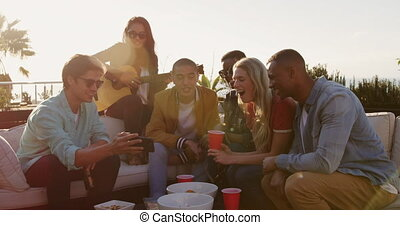 Group of friends drinking beers and discussing on a rooftop...