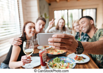 Group of friends eating and taking selfie at the table