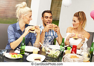 Group of friends eating hamburgers - Picture presenting...
